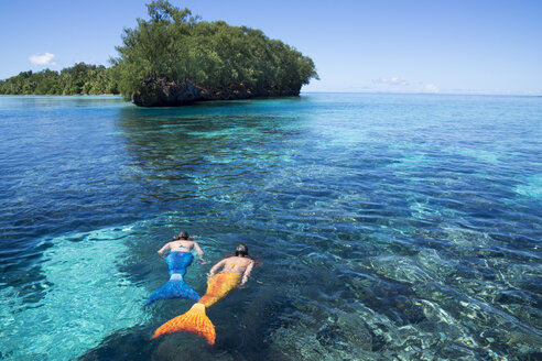 Palau, two young women in mermaid costume swimming in a lagoon - JWAF000104