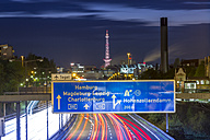 Germany, Berlin, Berlin-Charlottenburg, Federal Motorway 100 through downtown Berlin with the Funkturm Berlin and the exhibition halls in the background at night - NKF000151