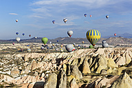 Turkey, Cappadocia, hot air balloons hoovering over tuff rock formations at Goereme National Park - SIE005518