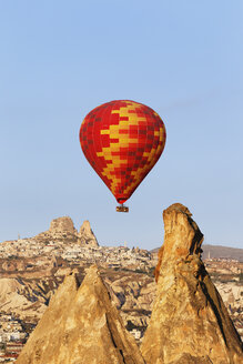 Turkey, Cappadocia, hot air balloon hoovering in front of the village Uchisar at Goereme National Park - SIEF005524