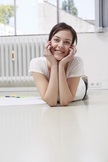 Smiling young woman lying on the floor - STKF000939