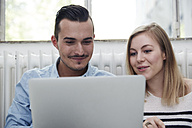 Smiling man and woman using laptop - STKF000993