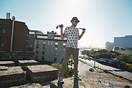 Young man with golf club looking over city, smiling - KOF000001