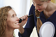 Daughter rouging her mother's face with make-up brush - STKF001051
