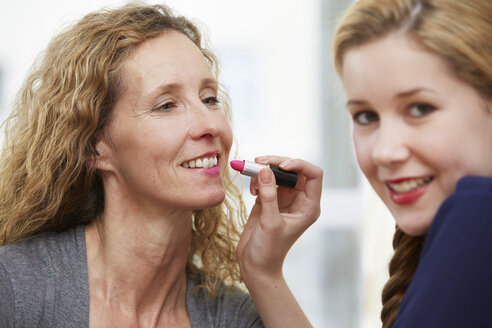 Daughter rouging her mother's lips - STKF001054