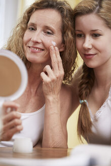 Mother applying face cream on her face while daughter looking - STKF001059
