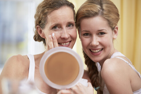 Portrait of mother and daughter heat to head with handheld mirror - STKF001061