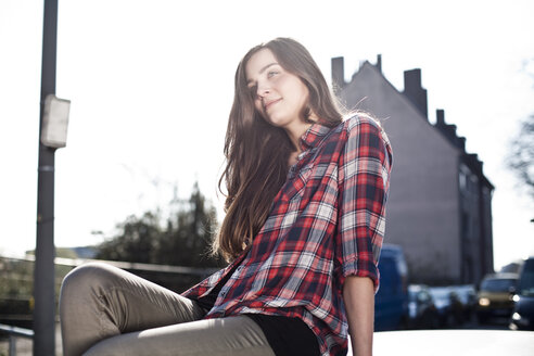 Smiling young woman sitting on car roof - FEXF000083