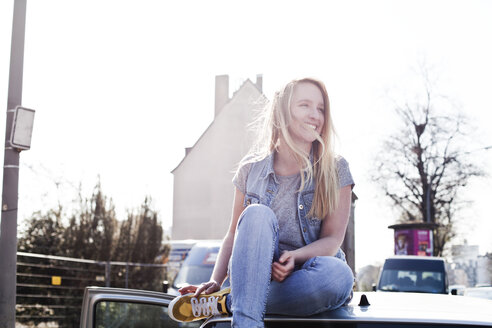 Smiling young woman sitting on car roof - FEXF000086