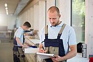 Craftsman in workshop taking notes - FKCF000013