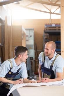 Two craftsmen with metal mugs talking - FKCF000026