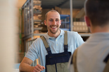 Smiling craftsman with colleague on shop floor - FKCF000048