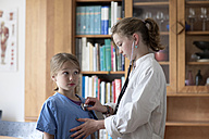 Brother and sister playing doctor with stethoscope and white coat - SGF000811