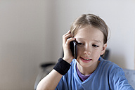 Portrait of boy telephoning with smartphone at home - SGF000809