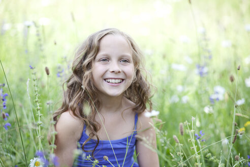 Portrait of smiling girl sitting on flower meadow - MAEF008561