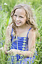 Portrait of smiling girl sitting on flower meadow - MAEF008562