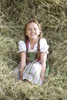 Germany, Bavaria, Girl in traditional dirndl sitting in hay - MAEF008565