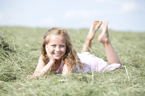 Germany, Bavaria, Young girl lying on meadow with hay - MAEF008569