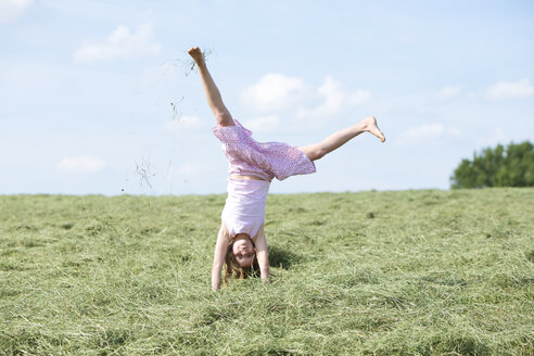 Germany, Bavaria, Young girl doing a cartwheel on meadow with hay - MAEF008570