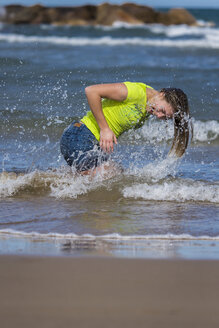 Female teenager tossing her wet hair at waterside of the beach - STSF000431