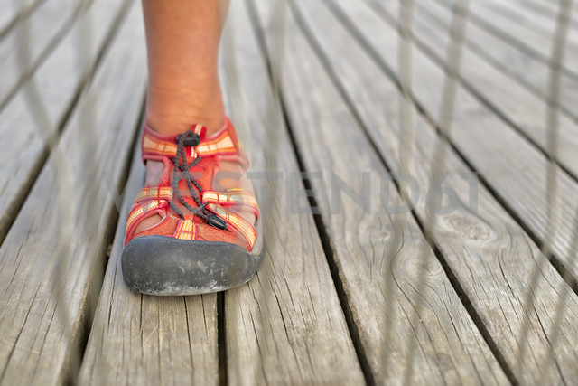 Foot with trekking sandal behind a fence on a boardwalk - SHF001524