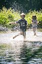 Germany, Landshut, Boy and girl running and splashing in brook - SARF000719