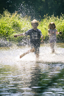 Germany, Landshut, Boy and girl running and splashing in brook - SARF000719
