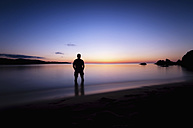 Spain, Menorca, Man watching sunset at Playa de Cavalleria - SMAF000215