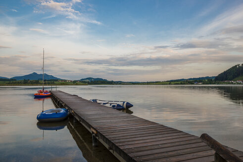 Germany, Bavaria, Fuessen, view to Hopfensee with jetty and rubber boats at twilight - WGF000358