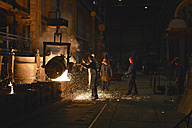 Germany, Saxony, workers racking the blast furnace in a foundry - LY000158