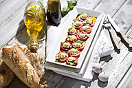 Slices of mozzarella cheese, tomatoes and basil herb on white plate - MAEF008676