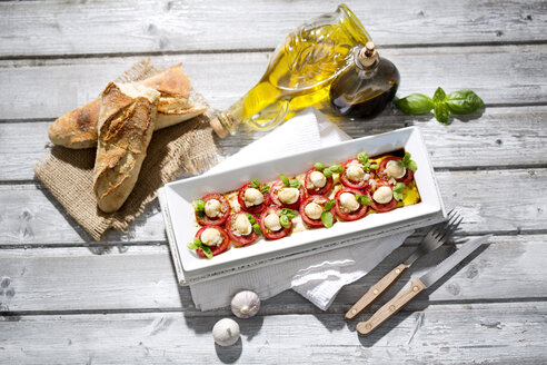 Slices of mozzarella cheese, tomatoes and basil herb on white plate - MAEF008677