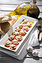 Slices of mozzarella cheese, tomatoes and basil herb on white plate - MAEF008678