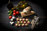 Slices of mozzarella cheese, tomatoes and basil herb - MAEF008679