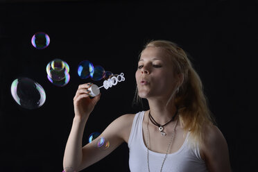 Young woman blowing soap bubbles - BFRF000472