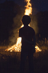 Boy standing in front camp fire at solstice - SARF000715