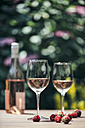 Two glasses of rose wine, wine bottle, strawberries and raspberries on wooden table - IPF000148