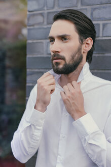 Portrait of young man folding up the collar of his shirt - MFF001145