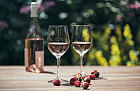 Two glasses of rose wine, wine bottle, strawberries and raspberries on wooden table - IPF000149
