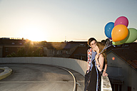 Teenage couple with balloons on parking ramp - FKF000570