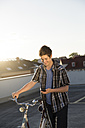 Teenage boy with bicycle and cell phone on parking lot - FKF000578