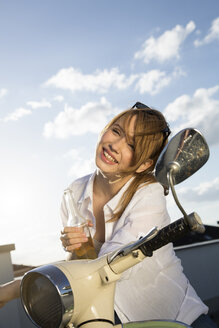 Happy teenage girl with bottle at moped - FKF000592