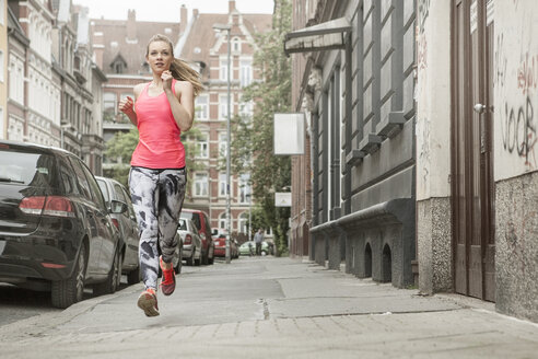 Germany, Lower Saxony, Hanover, young female jogger running on pavement - GCF000029