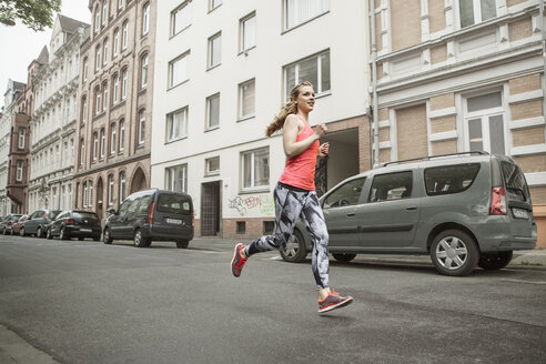 Germany, Lower Saxony, Hanover, young female jogger running on a street - GC000032