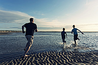 Netherlands, Ouddorp, Father with children running on beach - PAF000722