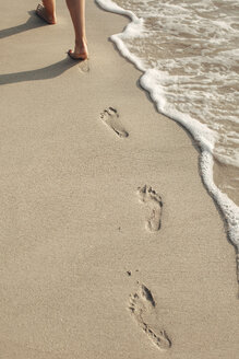 Indonesia, Gili Islands, woman walking on the beach leaving footprints, partial view - EBSF000243