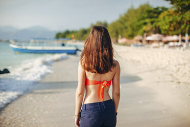 Indonesia, Gili Islands, woman standing on the beach, back view - EBSF000244