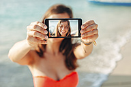 Indonesia, Gili Islands, woman on the beach showing smartphone with her selfie - EBSF000245