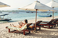 Indonesia, Gili Islands, woman lying on a beach chair reading a book - EBSF000247