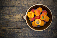 Bowl of sliced and whole apricots on wood, elevated view - LVF001533